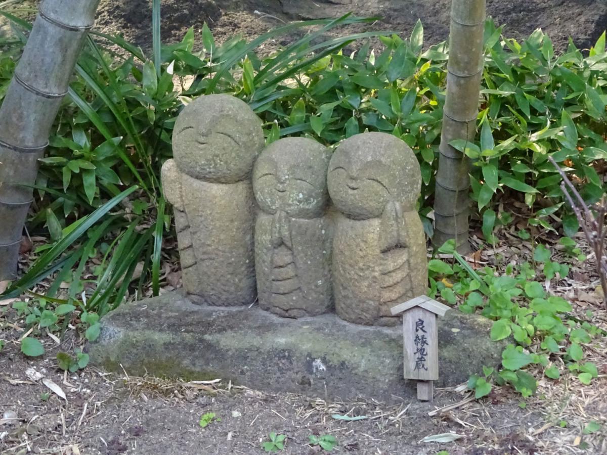 eine gruppe von drei grüßenden mönchsstatuen
