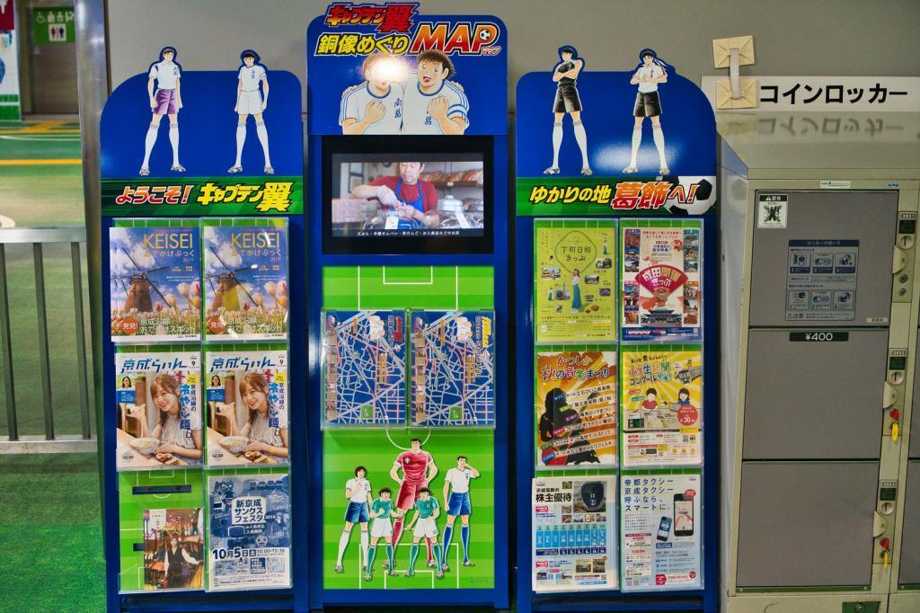 Stand mit kostenlosen Karten mit den Captain Tsubasa Statuen.