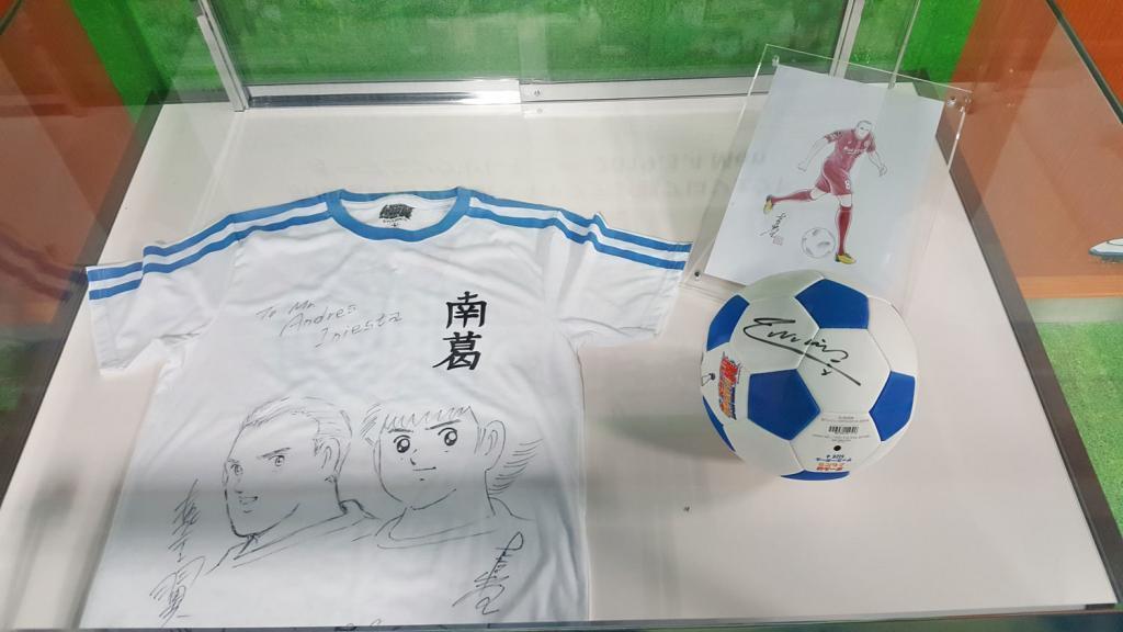 Captain Tsubasa Trikot und Fußball mit Unterschriften von Takahashi Yoichi und Andrés Iniesta.