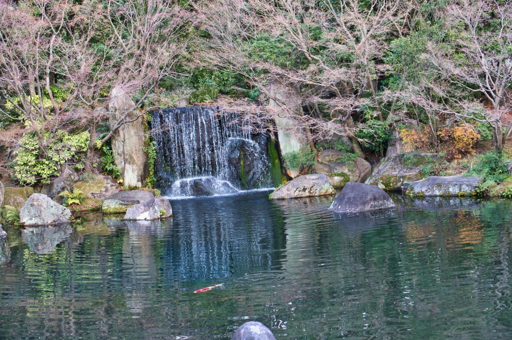 Teich mit Koi-Karpfen und einem Wasserfall im Koko-en Park in Himeji.