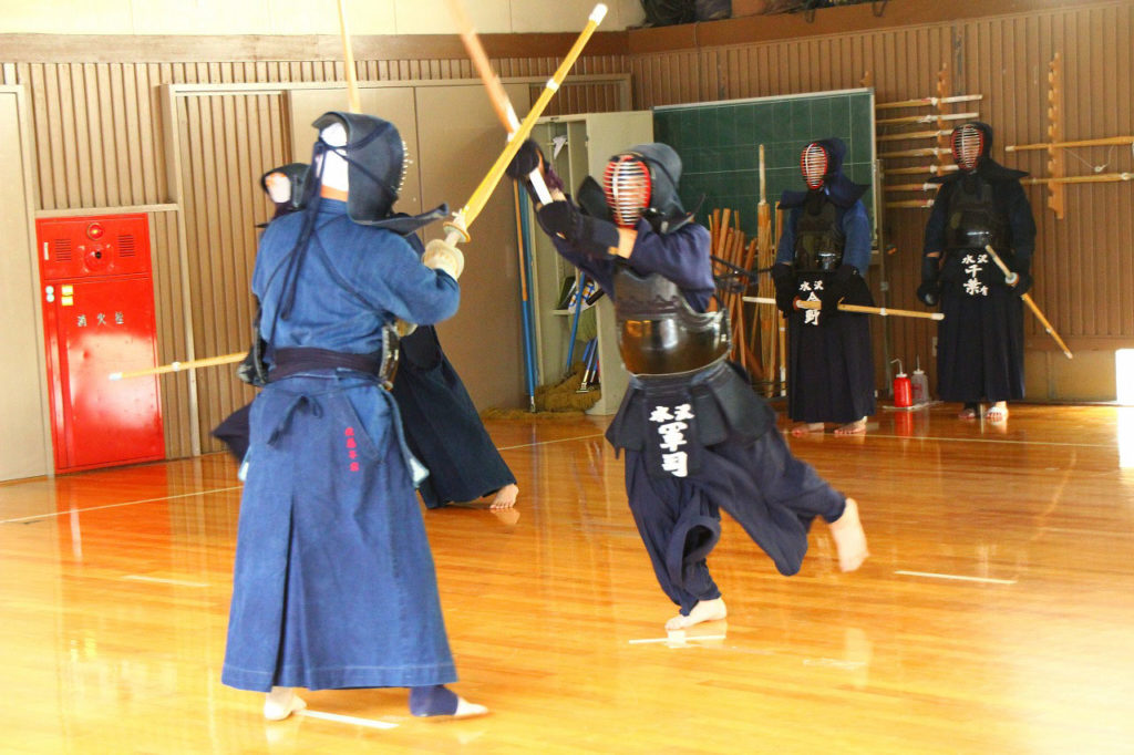 Kendo in einem Dojo in Japan. Zwei Kämpfer in Rüstung mit Shinai.